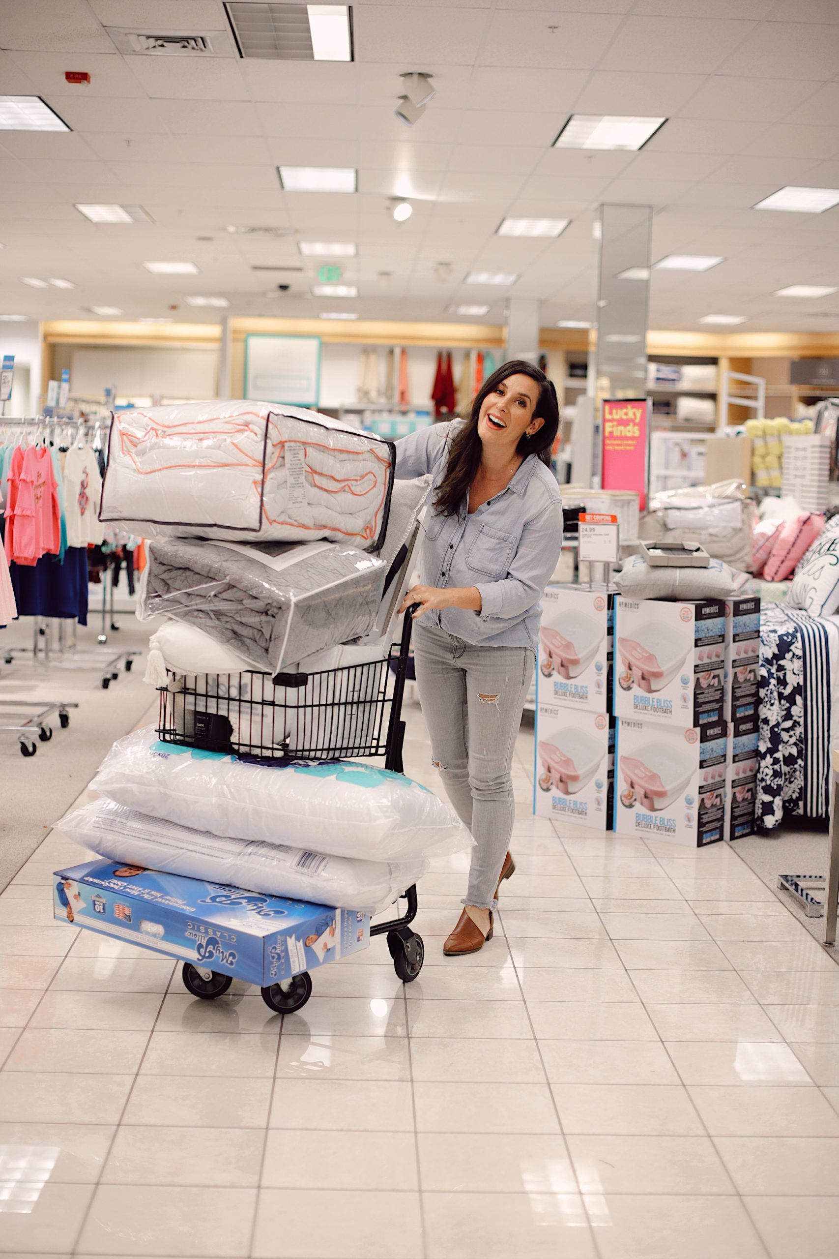 how to Make your Bed Comfortable Like a Hotel in 7 Easy Steps, a tutorial featured by top Florida lifestyle blog, Fresh Mommy Blog. Shopping throw pillows and bedding at Belk. | Best Bedding by popular Florida life and style blog, Fresh Mommy: image of a woman pushing a shopping cart full of packaged bedding.