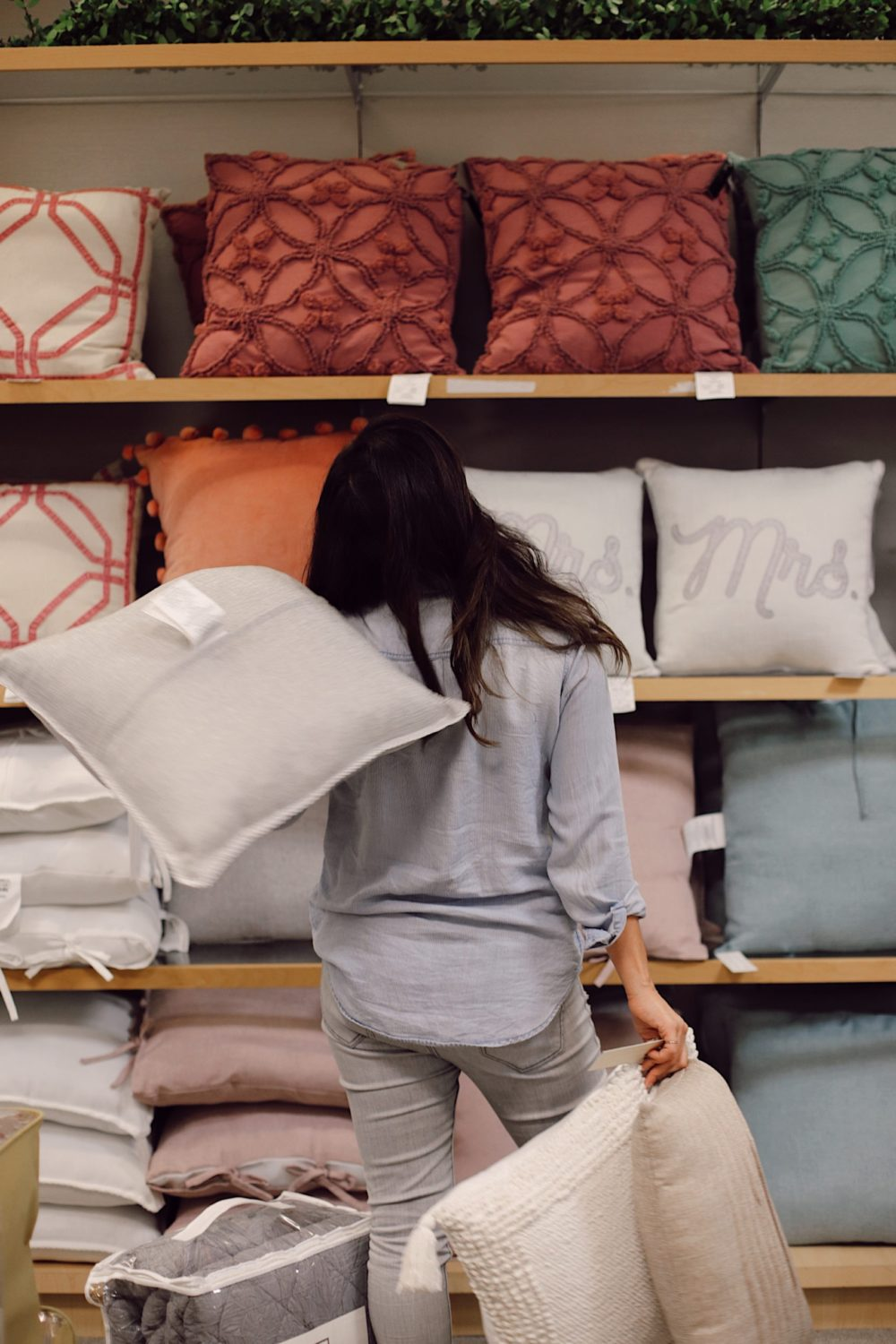 how to Make your Bed Comfortable Like a Hotel in 7 Easy Steps, a tutorial featured by top Florida lifestyle blog, Fresh Mommy Blog. Shopping throw pillows at Belk. | Best Bedding by popular Florida life and style blog, Fresh Mommy: image of a woman looking at a Belk pillow display.