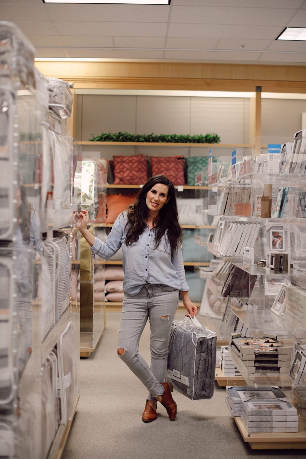 how to Make your Bed Comfortable Like a Hotel in 7 Easy Steps, a tutorial featured by top Florida lifestyle blog, Fresh Mommy Blog. | Best Bedding by popular Florida life and style blog, Fresh Mommy: image of a woman standing in a bedding aisle.