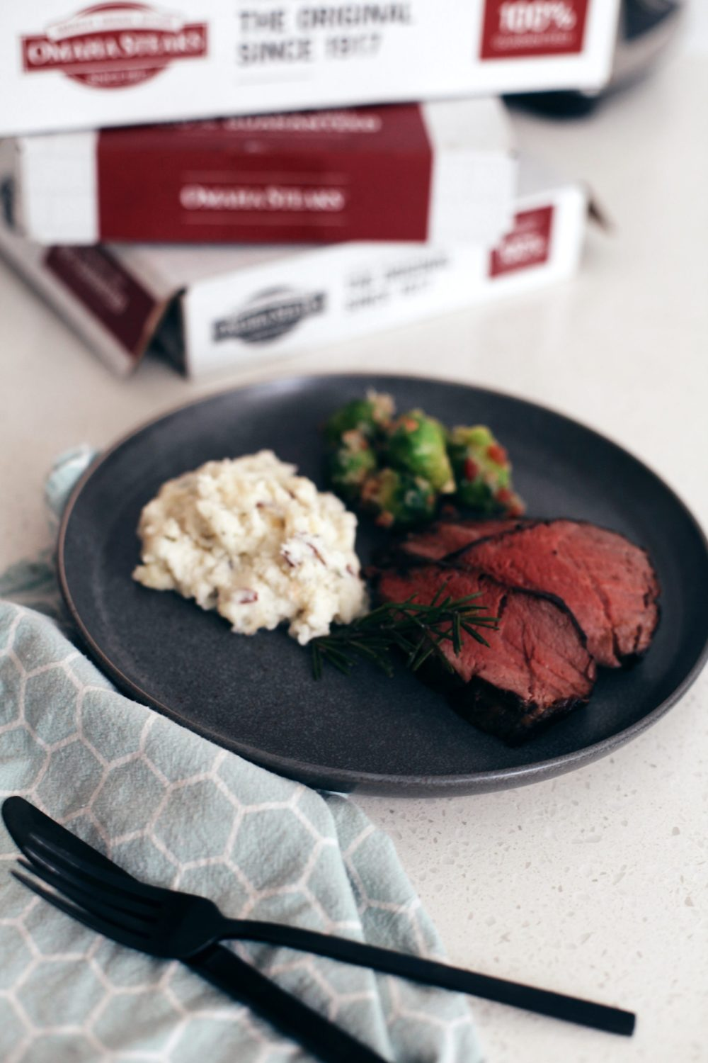 Best Way to Cook Beef Tenderloin with Espresso Crusted Chateaubriand Recipe from top Florida lifestyle blogger Tabitha Blue of Fresh Mommy Blog. How to get deliciously tender steak every time and the best coffee steak rub. | Best Beef Tenderloin by popular Florida lifestyle blog, Fresh Mommy Blog: image of the best Espresso Crusted Chateaubriand beef tenderloin on a plate with mashed potatoes and brussels sprouts.