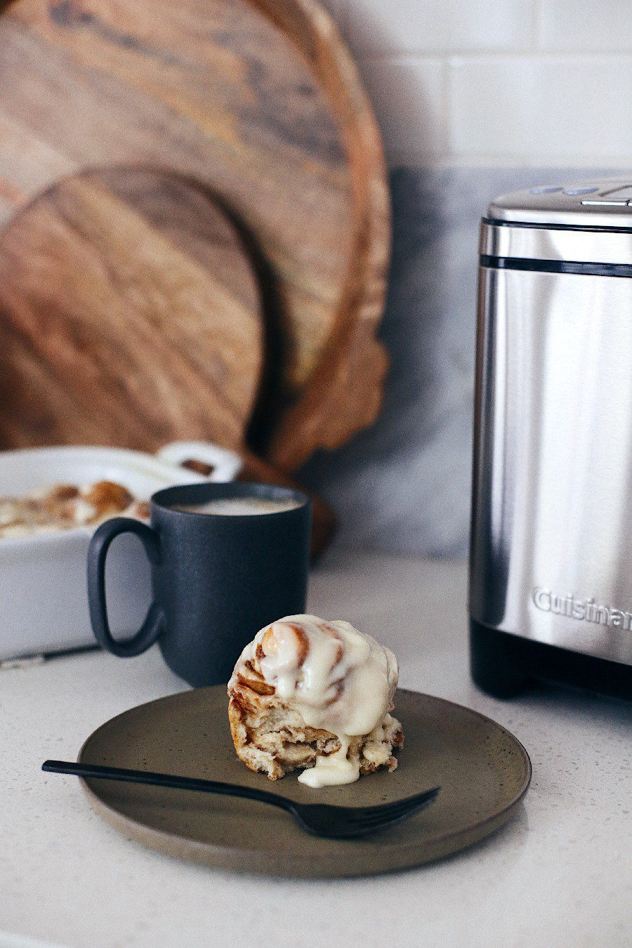 Easy bread machine cinnamon rolls dough. The best gooey sticky buns and clone of a Cinnabon roll icing! NO waiting overnight. Click for the recipe and how to video for fluffy cinnamon rolls homemade with a bread maker machine! Use all purpose flour or make them gluten free. Recipe from top Florida lifestyle blogger Tabitha Blue of Fresh Mommy Blog. | Bread Machine Cinnamon Roll Recipe by popular Florida lifestyle blog, Fresh Mommy Blog: image of a cinnamon roll on a grey plate next to some cinnamon rolls in a white ceramic baking dish next to a bowl of cream cheese icing.