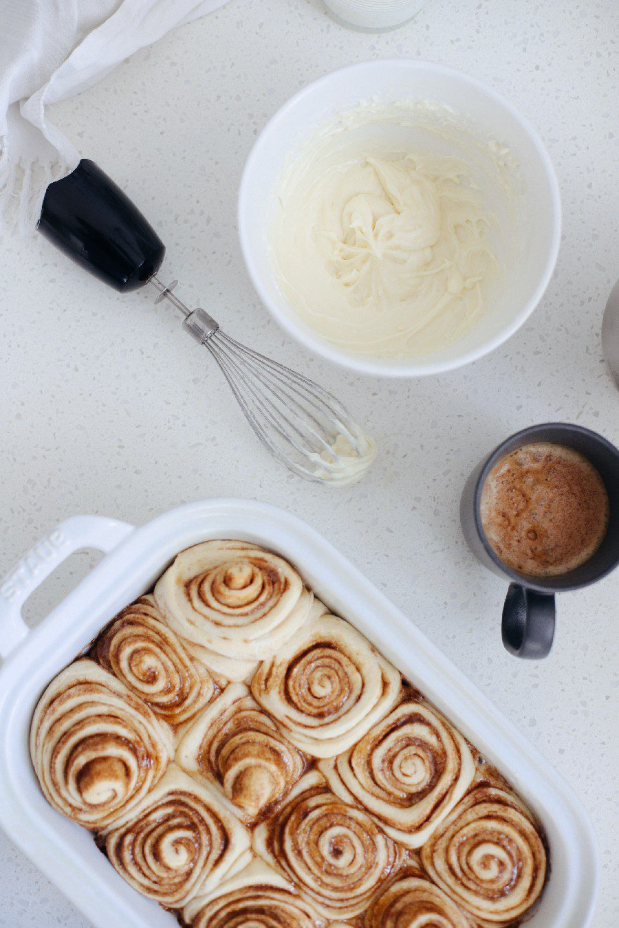 Easy bread machine cinnamon rolls dough. The best gooey sticky buns and clone of a Cinnabon roll icing! NO waiting overnight. Click for the recipe and how to video for fluffy cinnamon rolls homemade with a bread maker machine! Use all purpose flour or make them gluten free. Recipe from top Florida lifestyle blogger Tabitha Blue of Fresh Mommy Blog. | Bread Machine Cinnamon Roll Recipe by popular Florida lifestyle blog, Fresh Mommy Blog: image of cinnamon rolls in a white ceramic baking dish next to a bowl of cream cheese icing.
