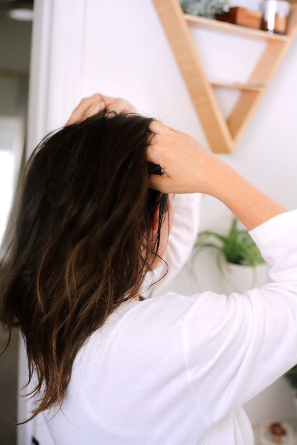 DIY Hair Growth Oil with Essential Oils Perfect for Postpartum Hair Fall. This healthy DIY scalp oil for hair growth is loaded with essential oils that boast anti-inflammatory and anti-bacterial properties that help in combating hair fall, stimulating the scalp for growth and more. |  DIY Hair Growth Oil by popular Florida beauty blog, Fresh Mommy Blog: image of a woman rubber her fingers on her scalp.
