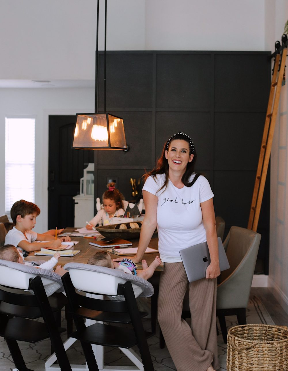 How to Survive Working With Kids at Home - Tips for making the most of working from home with kids homeschooling. Click through for tips from lifestyle blogger Tabitha Blue of Fresh Mommy Blog! | Working From Home With Kids by popular Florida lifestyle blog, Fresh Mommy Blog: image of a mom standing at the table with her kids as they do homeschooling work.
