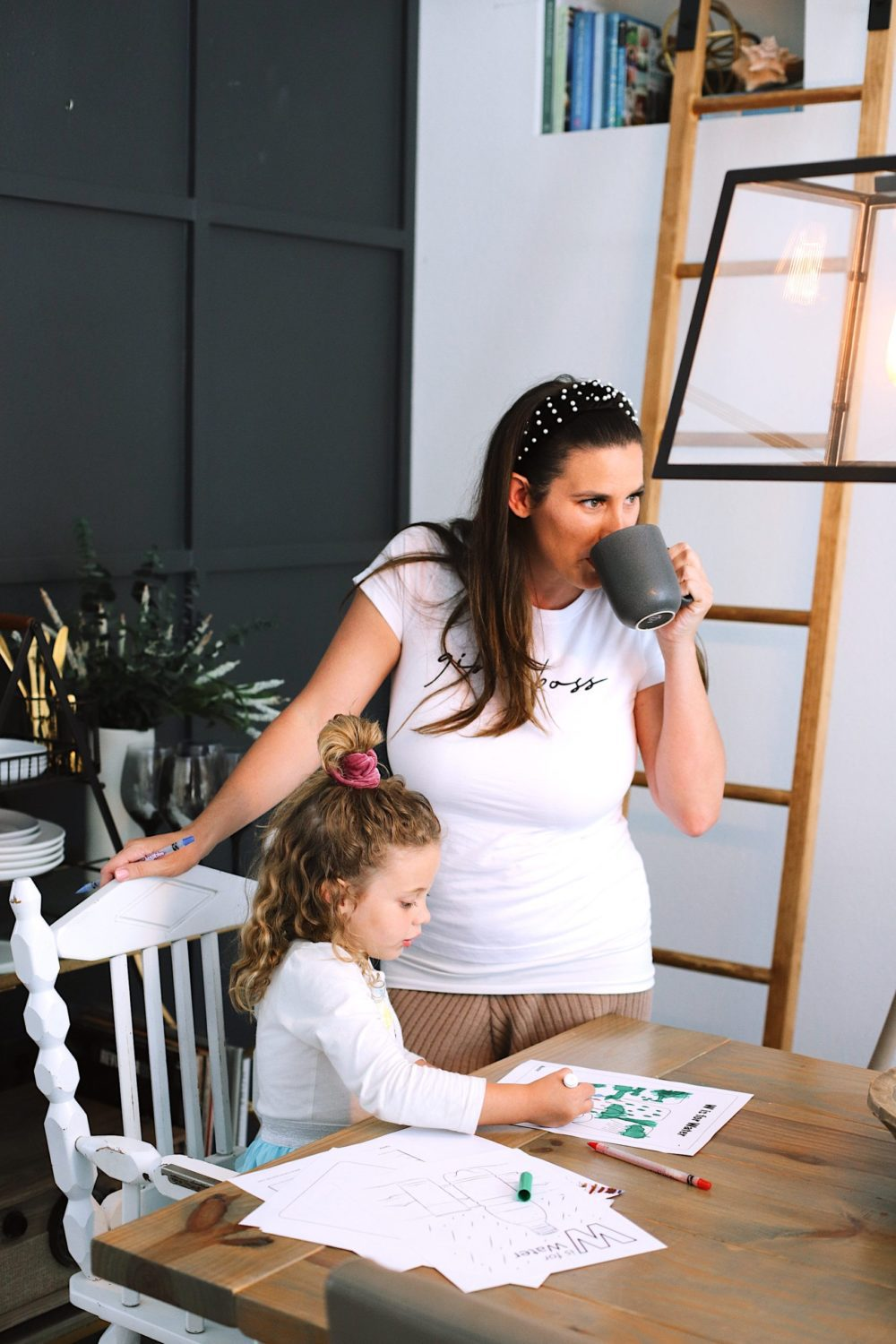 How to Survive Working With Kids at Home - Tips for making the most of working from home with kids homeschooling. Click through for tips from lifestyle blogger Tabitha Blue of Fresh Mommy Blog! | Working From Home With Kids by popular Florida lifestyle blog, Fresh Mommy Blog: image of a mom standing next to her daughter as she sits at the table and does homeschooling work.