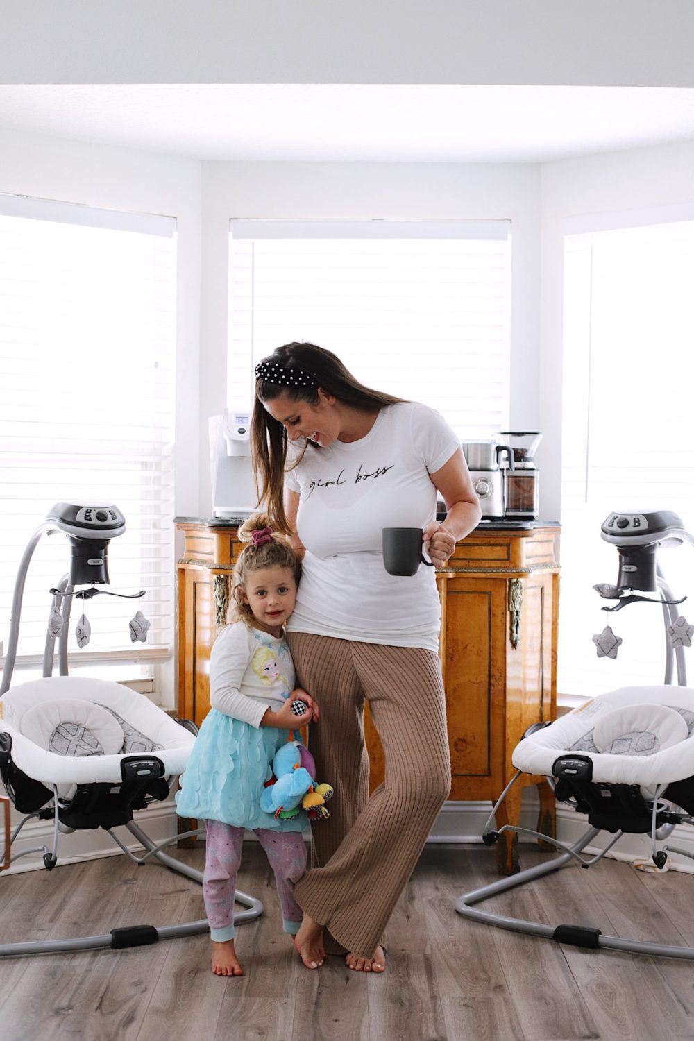 How to Survive Working With Kids at Home - Tips for making the most of working from home with kids homeschooling. Click through for tips from lifestyle blogger Tabitha Blue of Fresh Mommy Blog! | Working From Home With Kids by popular Florida lifestyle blog, Fresh Mommy Blog: image of a mom holding a cup of coffee while her young daughter hugs her leg.