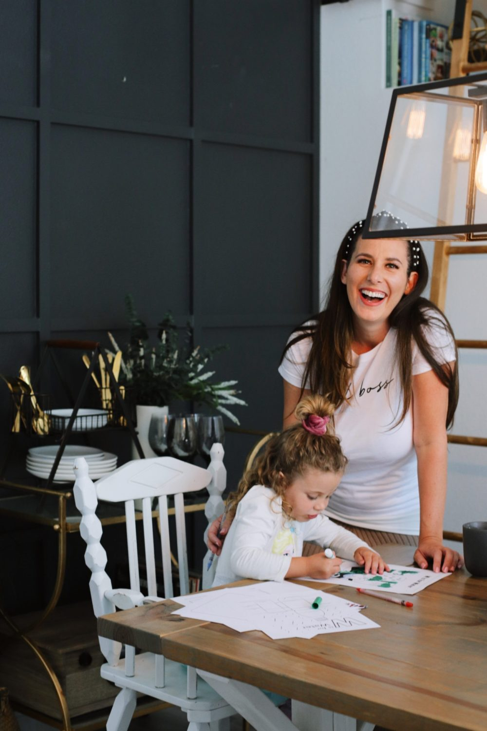 How to Survive Working With Kids at Home | Working From Home With Kids by popular Florida lifestyle blog, Fresh Mommy Blog: image of a woman standing next to her young daughter while she does school work at the table.