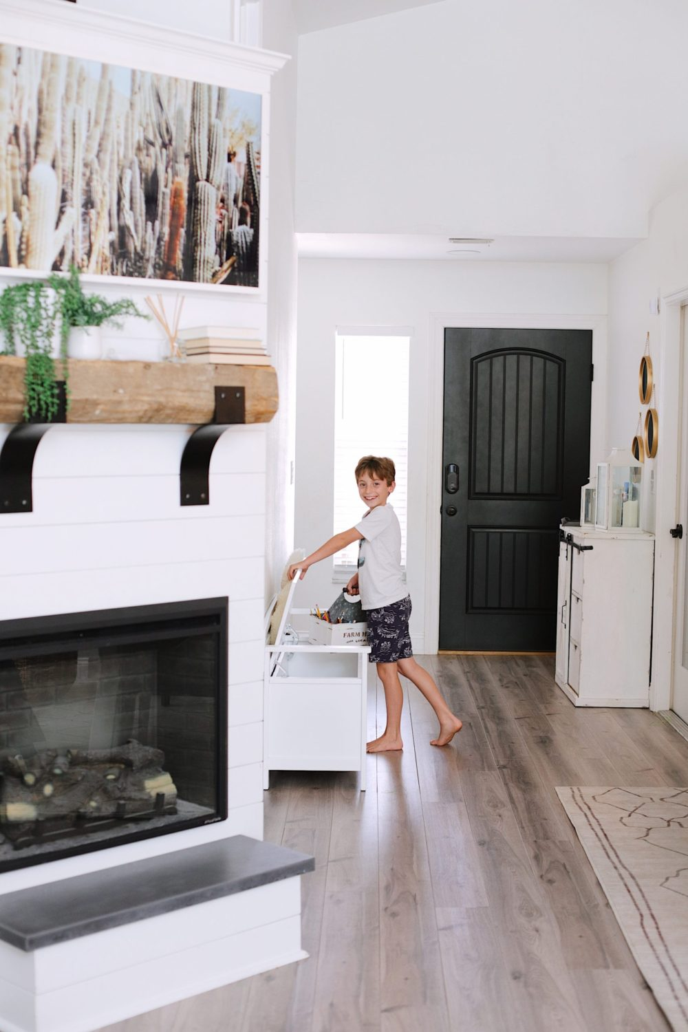 How to Survive Working With Kids at Home - Find creative storage solutions for all the at home school work and office supplies while working from home. Click through for more tips! | Working From Home With Kids by popular Florida lifestyle blog, Fresh Mommy Blog: image of a boy placing homeschooling supplies in a Bed Bath and Beyond Laredo Storage Bench in White.
