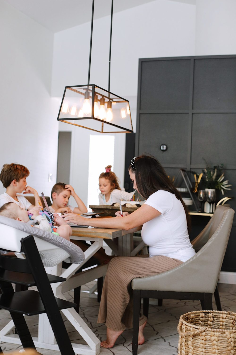 How to Survive Working With Kids at Home - Tips for making the most of working from home with kids homeschooling. Click through for tips from lifestyle blogger Tabitha Blue of Fresh Mommy Blog! | Working From Home With Kids by popular Florida lifestyle blog, Fresh Mommy Blog: image of a mom sitting at the table with her kids as they do homeschooling work.