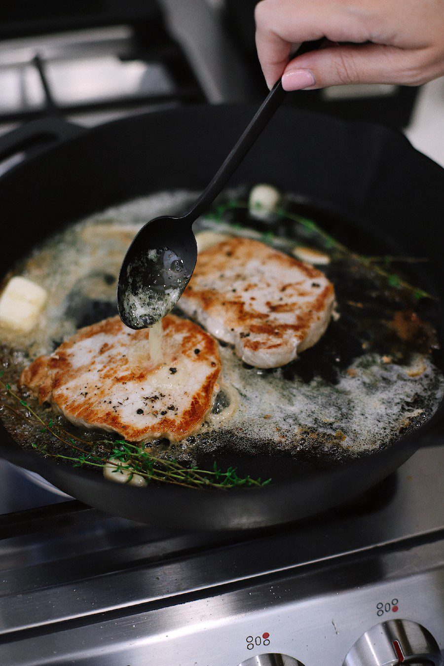How To Cook Tender Skillet Pork Chops in the Oven What if I told you we figured out how to make sure to get those tender, juicy skillet pork chops every time, with a quick roast in the oven? Ready to say goodbye to dry, flavorless chops? These tips will have you adding tender pork chops back to your rotation. Try our pork chop recipe with browned butter garlic sauce!   Skillet Pork Chops by popular Florida lifestyle blog, Fresh Mommy Blog: image of a woman cooking skillet pork chops in her kitchen.