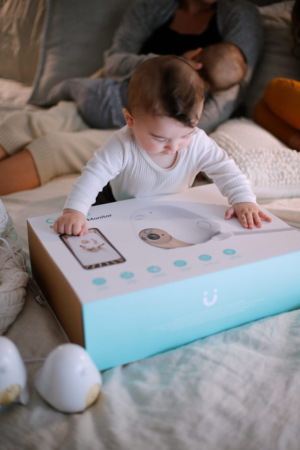 Best Baby Monitor by popular Florida motherhood blog, Fresh Mommy Blog: image of a mom holding her twin babies on a bed next to a Cubo Ai monitor box.