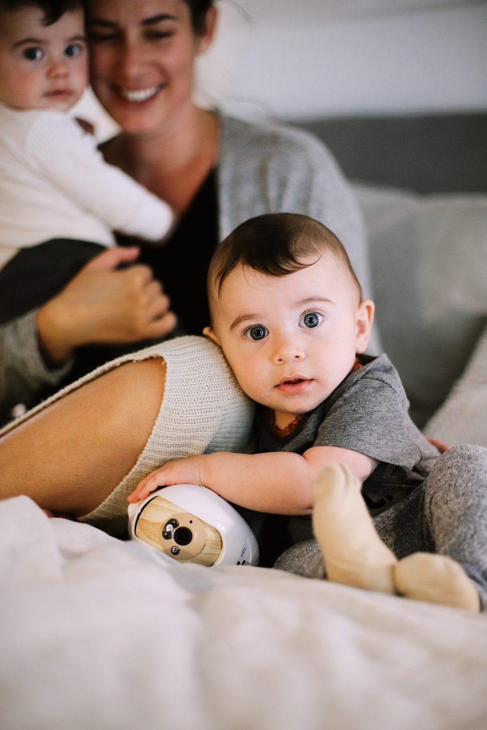 Best Baby Monitor by popular Florida motherhood blog, Fresh Mommy Blog: image of a mom holding her twin babies on a bed next to a Cubo Ai monitor.