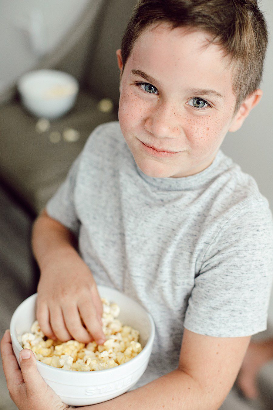 10 Popcorn Games for a Great Family Fun Night | Family Fun Night by popular Florida lifestyle blog, Fresh Mommy Blog: image of a young boy holding a bowl of popcorn.