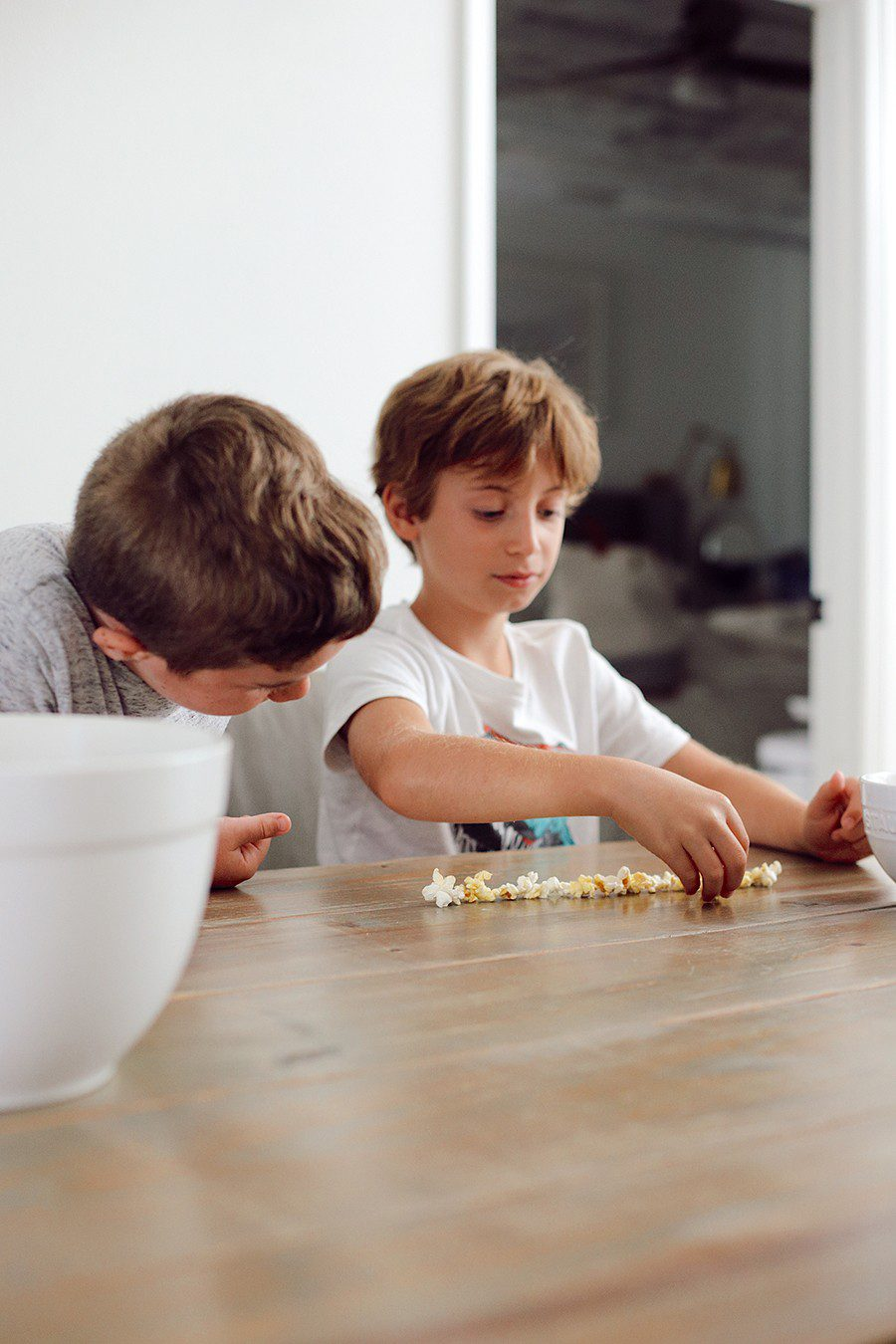 Popcorn charades and more popcorn games for family game night! | Family Fun Night by popular Florida lifestyle blog, Fresh Mommy Blog: image of two boys lining up some popcorn on a table.