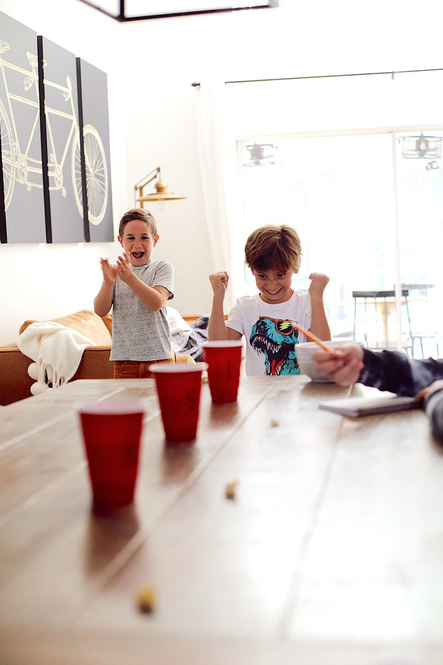 Popcorn toss and more fun popcorn games for family game night! | Family Fun Night by popular Florida lifestyle blog, Fresh Mommy Blog: image of some kids tossing popcorn into red plastic cups.