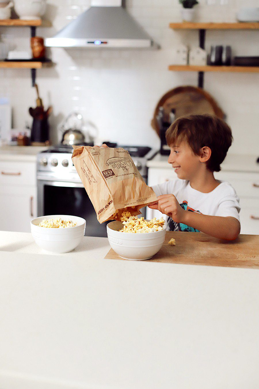 10 Popcorn Games for a Great Family Fun Night | Family Fun Night by popular Florida lifestyle blog, Fresh Mommy Blog: image of a boy dumping Orville Redenbacher's microwave popcorn into white bowls.