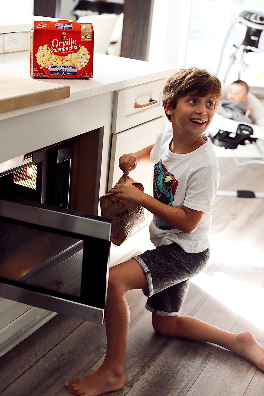 10 Popcorn Games for a Great Family Fun Night | Family Fun Night by popular Florida lifestyle blog, Fresh Mommy Blog: image of a boy holding a bag of Orville Redenbacher's microwave popcorn next to a open microwave.
