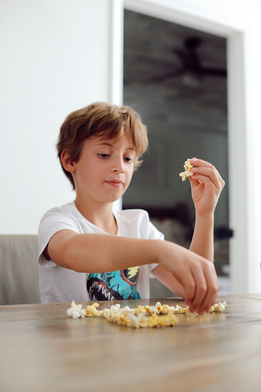 Popcorn charades and more popcorn games for family game night! | Family Fun Night by popular Florida lifestyle blog, Fresh Mommy Blog: image of a boy making a shape on a table out of popcorn.