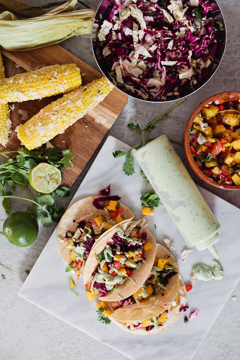 Blackened Fish Tacos with Mango Salsa, Cilantro Lime Sauce and Mexican Street Corn! It's SO good (even approved from someone who doesn't really like fish)