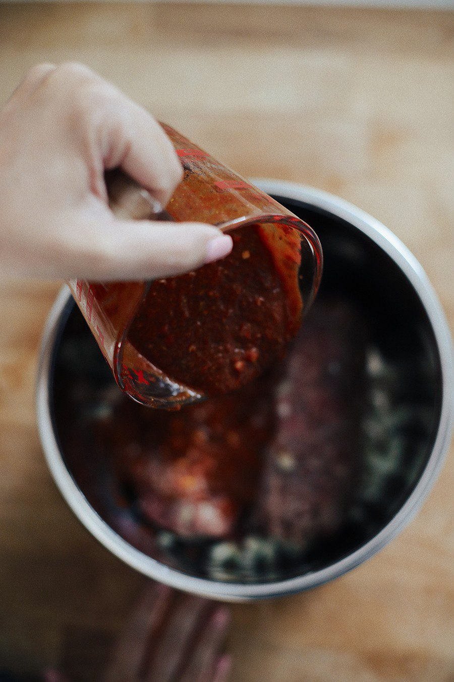 Easy Weeknight Crockpot Meals: Slow Cooker Barbacoa Beef Tacos   Omaha Steaks by popular Florida lifestyle blog, Fresh Mommy Blog: image of a woman pouring a marinade on some raw beef in a slow cooker.