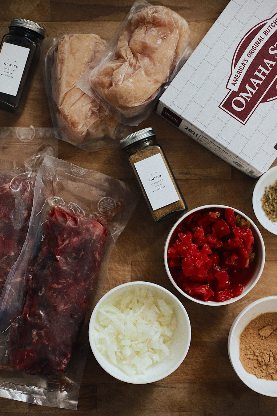 Easy Weeknight Crockpot Meals: Slow Cooker Barbacoa Beef Tacos   Omaha Steaks by popular Florida lifestyle blog, Fresh Mommy Blog: image of a Omaha Steaks box, vacuum sealed beef, chopped white onions, ground cumin, and diced tomatoes.