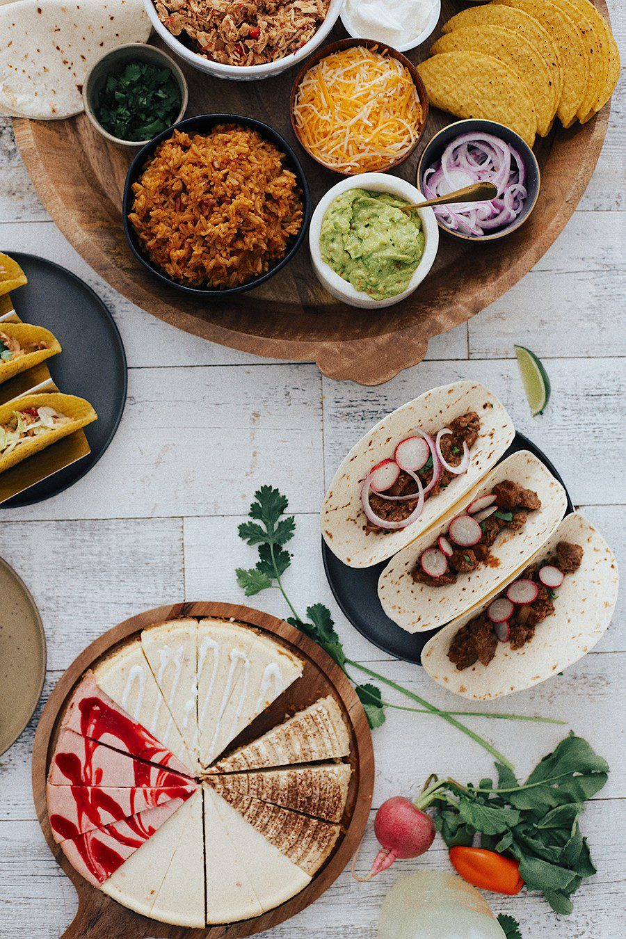 Easy Weeknight Crockpot Meals: Slow Cooker Barbacoa Beef Tacos   Omaha Steaks by popular Florida lifestyle blog, Fresh Mommy Blog: image of barbacoa beef tacos, sliced cheesecake, guacamole, red onions, grated cheese, hard taco shells, sour cream, black olives, and tortillas.