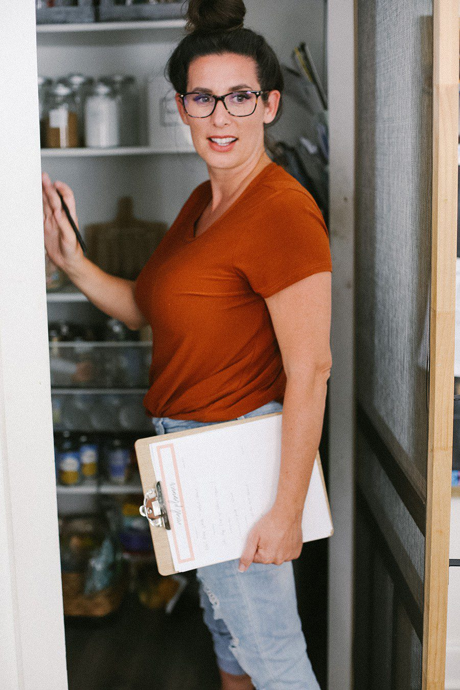 Family Meal Planning Tips to Save Money and Free Printable | Family Meal Planning by popular Florida lifestyle blog, Fresh Mommy Blog: image of a woman standing in her pantry, wearing a read t-shirt and distressed denim and holding a clipboard.