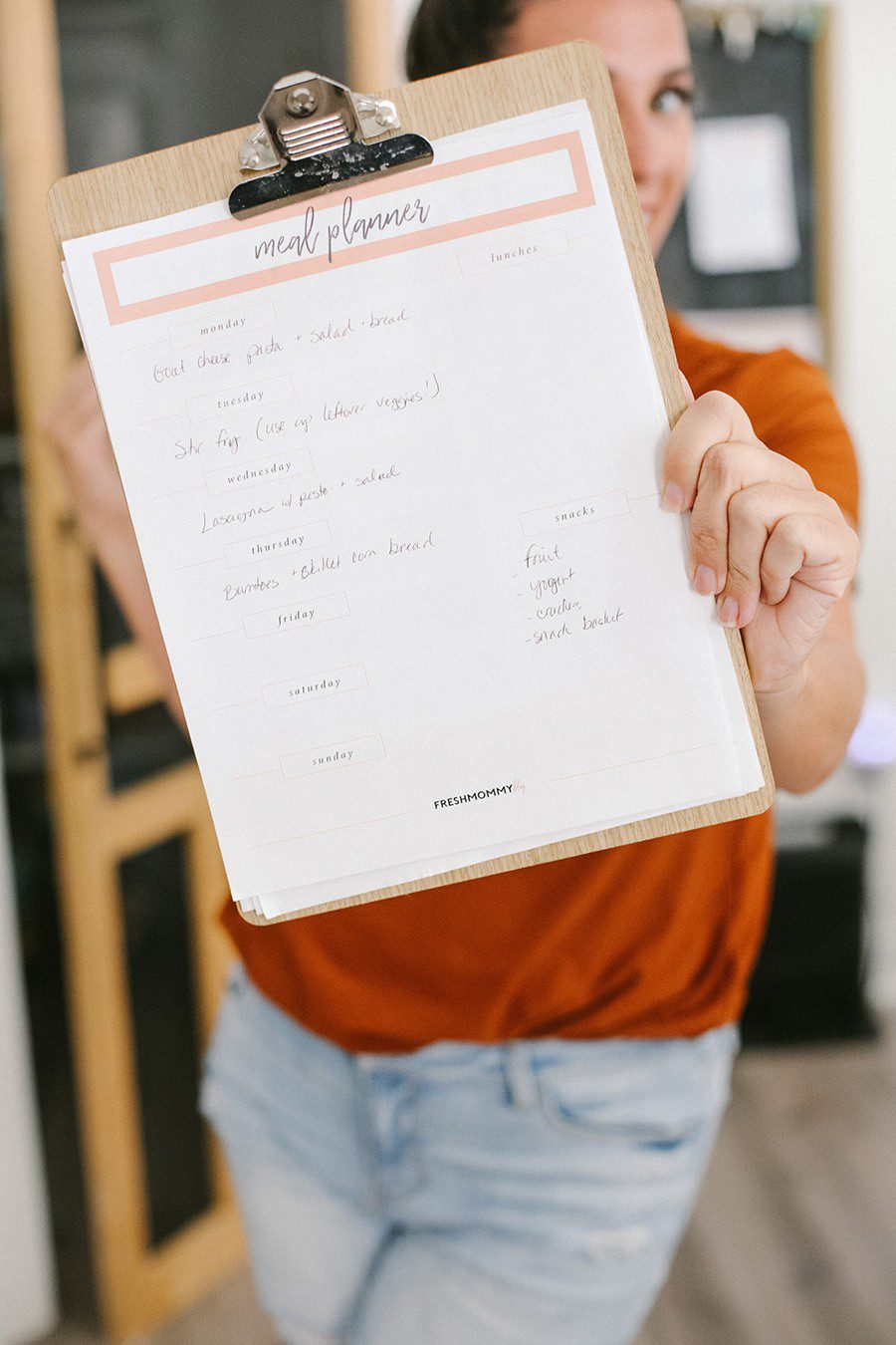 Family Meal Planning Tips to Save Money and Free Printable | Family Meal Planning by popular Florida lifestyle blog, Fresh Mommy Blog: image of a woman holding a clipboard with a meal planner sheet on it.