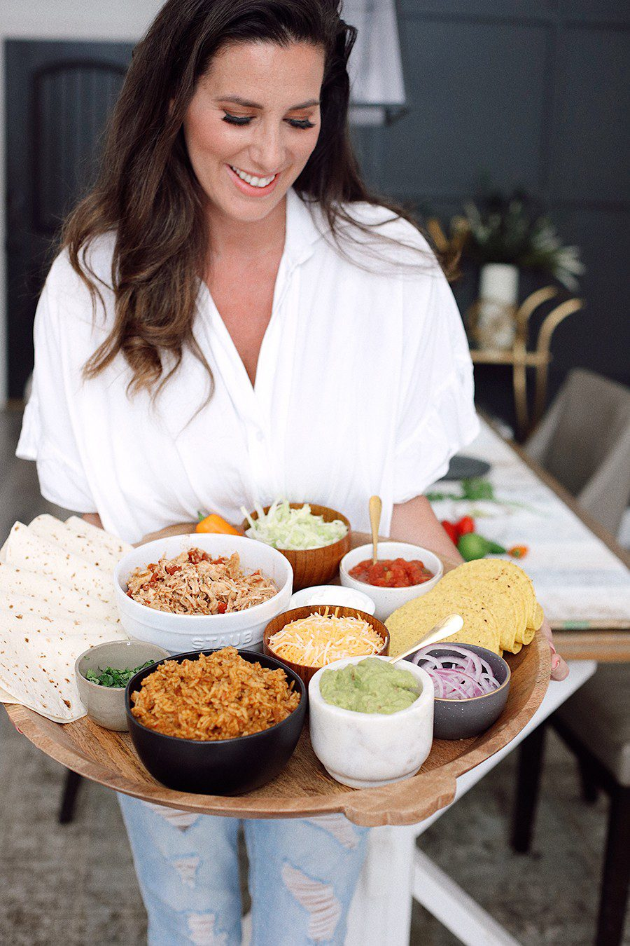 How to make an epic taco board and taco party platter tips! Plus, the best slow cooker taco chicken recipe! | Chicken Tacos by popular Florida lifestyle blog, Fresh Mommy Blog: image of Tabitha Blue holding a Chicken Tacos platter.