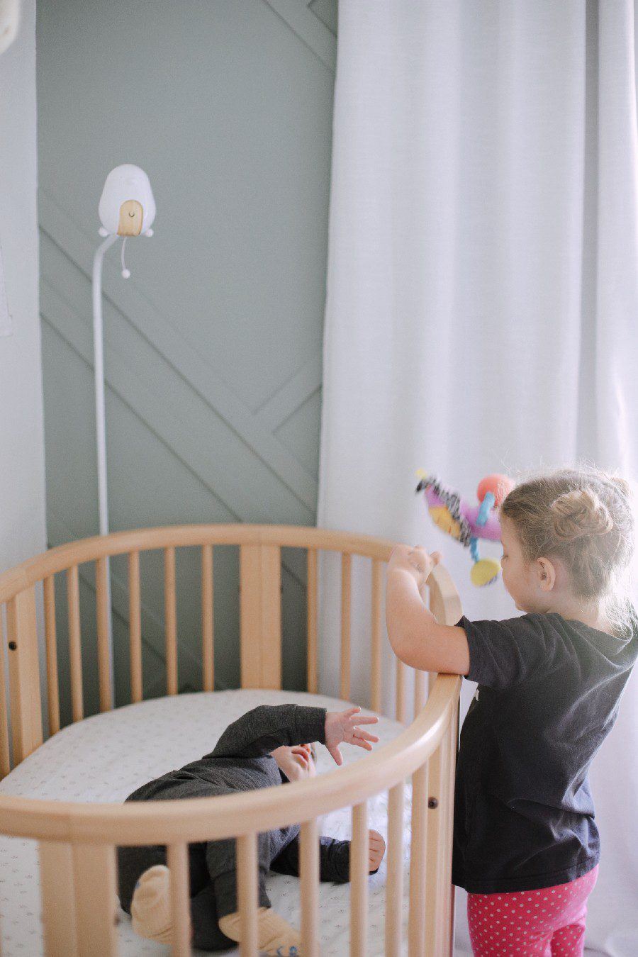 Big sister playing with baby in the stokke sleepi crib. The Best Baby Monitor for Twins - Cubo Ai Smart Baby Monitor Review  Best Baby Monitor by popular Florida motherhood blog, Fresh Mommy Blog: image of a little girl standing next to a baby laying in a stokke sleepi crib.