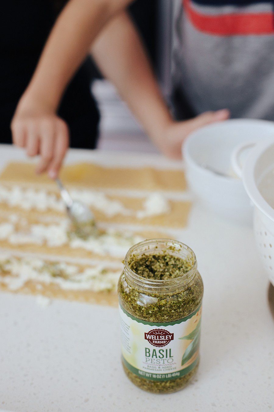 Cast Iron Lasagna by popular Florida lifestyle blog, Fresh Mommy Blog: image of a mom and her son placing ricotta cheese and pesto sauce on lasagna noodles.