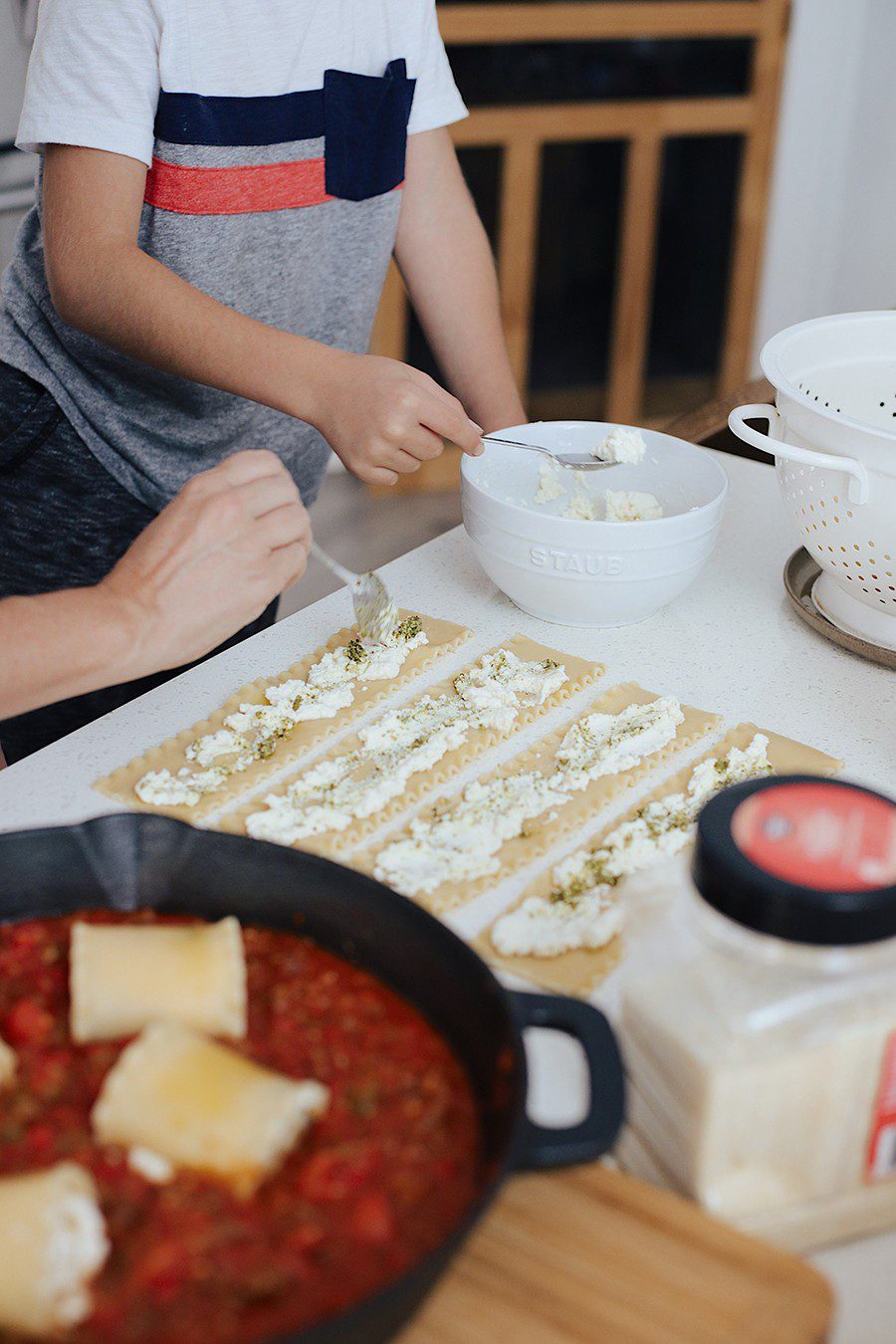 mom and son cooking lasagna together | Cast Iron Lasagna by popular Florida lifestyle blog, Fresh Mommy Blog: image of a mom and her son putting ricotta cheese on lasagna noodles.