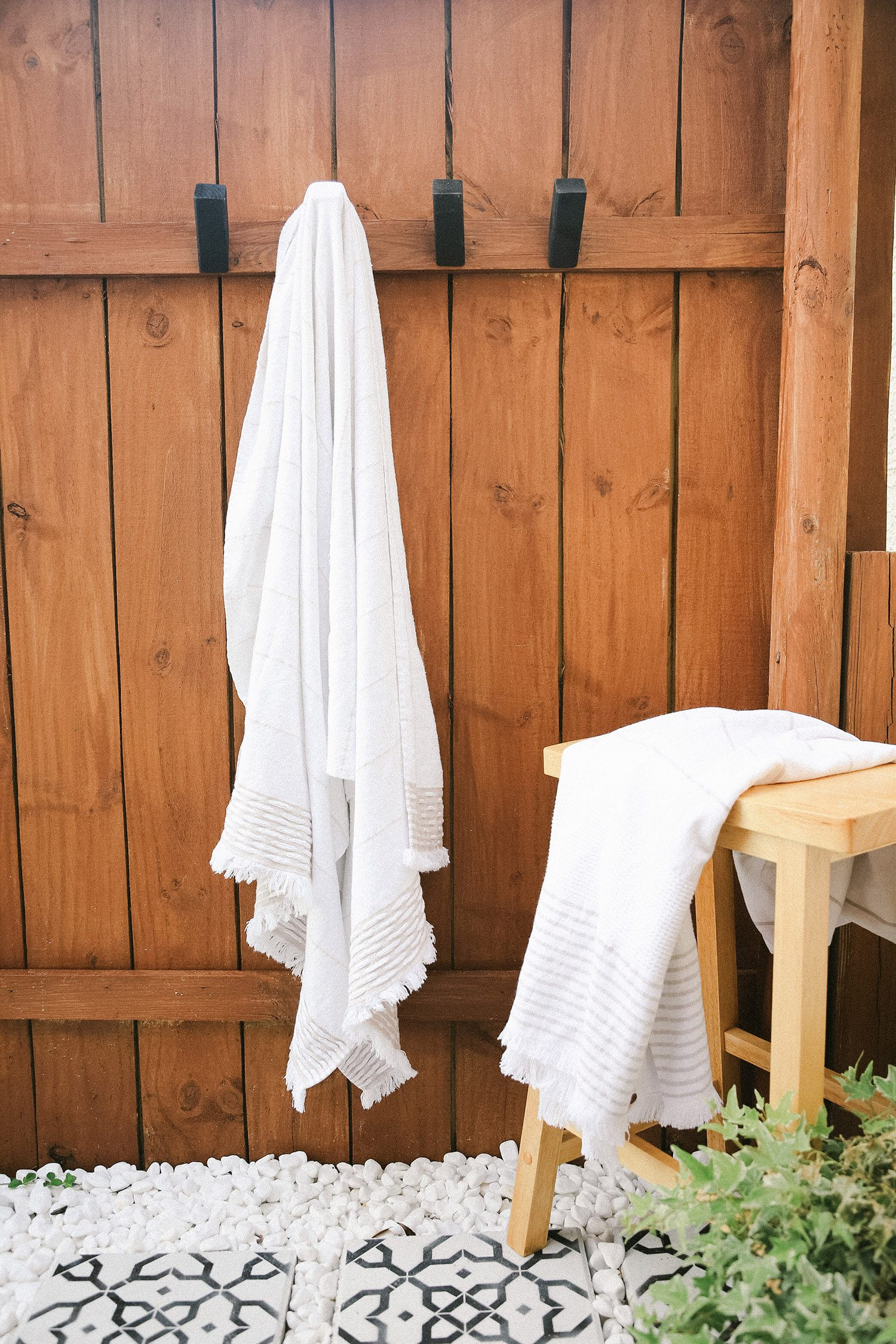 DIY Outdoor Shower Ideas on a Budget for the Ultimate Backyard Oasis   DIY Outdoor Shower by popular Florida DIY blog, Fresh Mommy Blog: image of a DIY outdoor shower with white towels hanging on black wooden towel hooks.