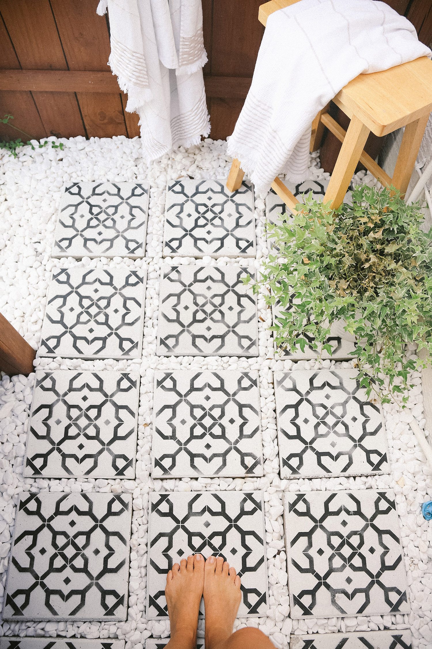 DIY Outdoor Shower Ideas on a Budget for the Ultimate Backyard Oasis   DIY Outdoor Shower by popular Florida DIY blog, Fresh Mommy Blog: image of a DIY outdoor shower with black and white mosaic tile and white rocks.