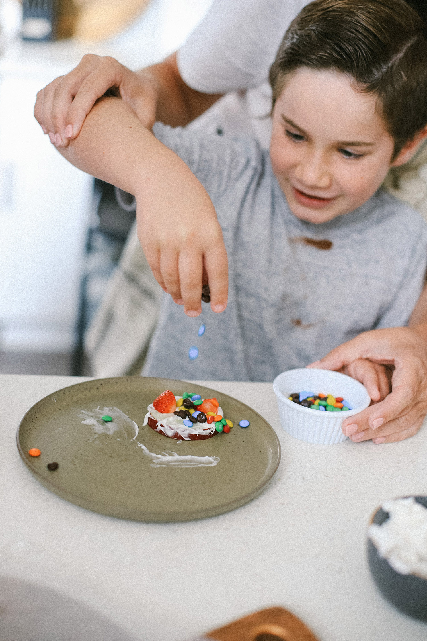 Easy snack ideas for a healthy sweet snacktivity for kids! Apple Donut fun recipe for kids from top Florida blogger Tabitha Blue of Fresh Mommy Blog | Apple Donuts by popular Florida motherhood blog, Fresh Mommy Blog: image of a young boy putting mini M&Ms on a apple slice.