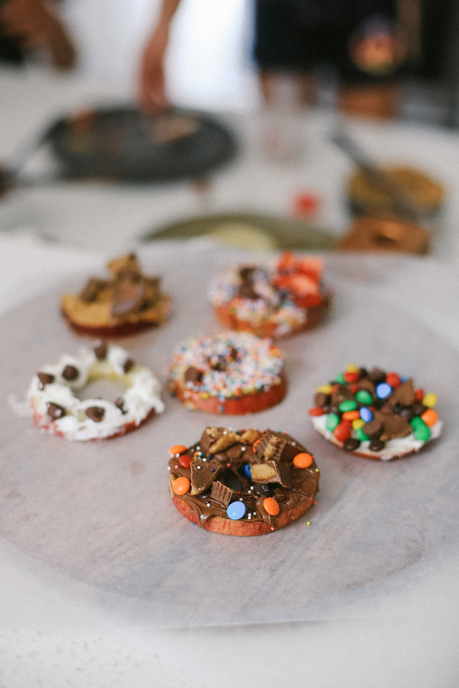 Easy snack ideas for a healthy sweet snacktivity for kids! Apple Donut fun recipe for kids from top Florida blogger Tabitha Blue of Fresh Mommy Blog | Apple Donuts by popular Florida motherhood blog, Fresh Mommy Blog: image of apple slices on a plate topped with things like Nutella, sprinkles, marshmallow fluff, chocolate chips, and peanut butter fluff.