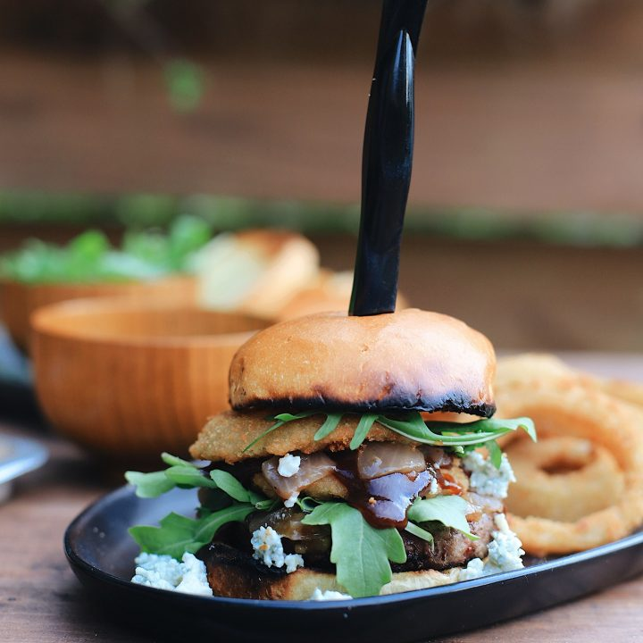 BBQ Bacon Blue Burger for a Tasty Backyard Barbecue. Not your average burger! Juicy beef burgers seasoned with a the perfect amount of spice, topped with smoked bacon jam, sweet bourbon onions, arugula, blue cheese, onion rings, BBQ sauce and a buttery grilled bun!
