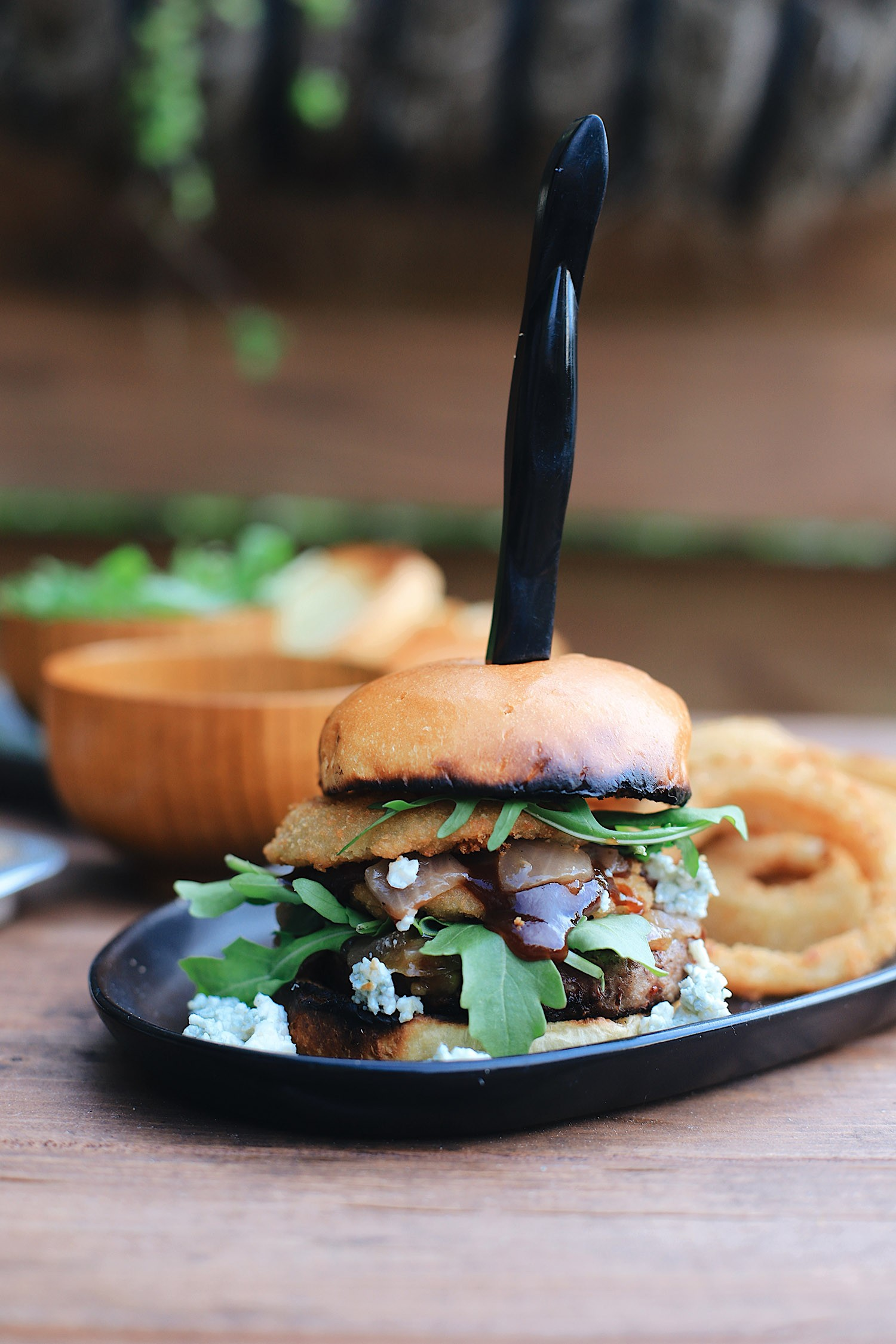 BBQ Bacon Blue Burger for a Tasty Backyard Barbecue. Not your average burger! Juicy beef burgers seasoned with a the perfect amount of spice, topped with smoked bacon jam, sweet bourbon onions, arugula, blue cheese, onion rings, BBQ sauce and a buttery grilled bun!   Grilling Season by popular Florida lifestyle blog, Fresh Mommy Blog: image of a BBQ burger on a black oval plate next to some onion rings.