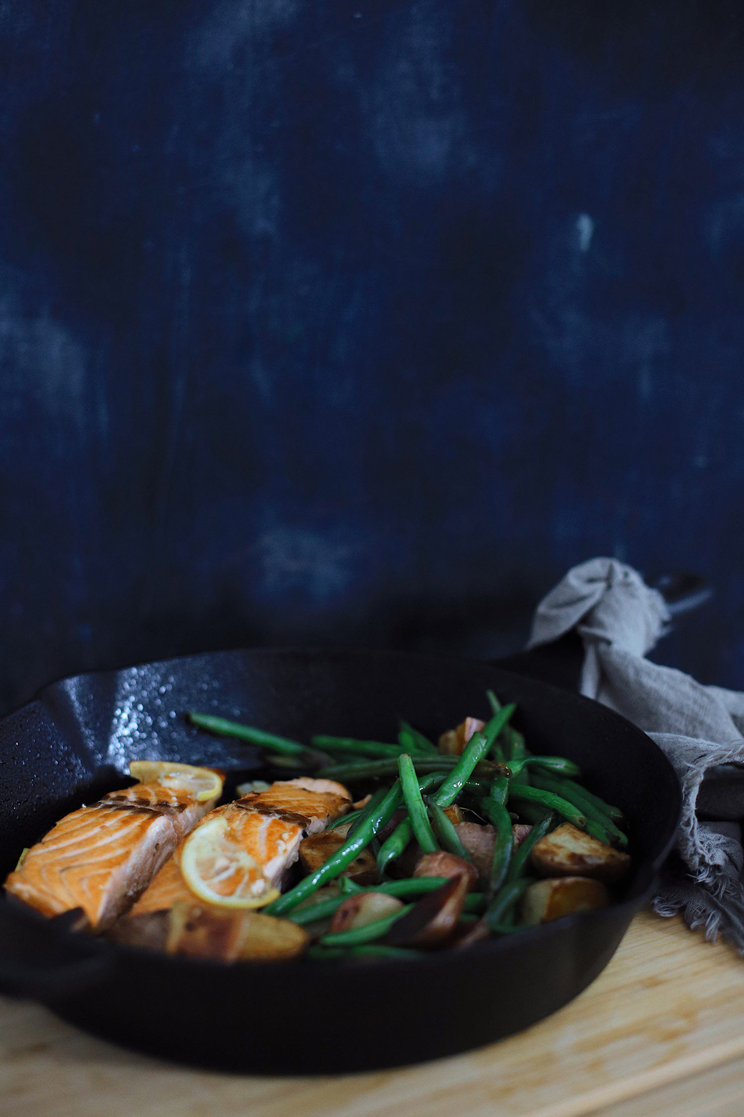 Wondering how to cook salmon? We've got such a simple and easy cast iron skillet salmon recipe with a delicious garlic lemon butter glaze. Pan seared salmon is an easy way to get it just right, every time… in fact, a kid can do it! | Salmon Skillet by possible Florida lifestyle blog, Fresh Mommy Blog: image of salmon, green beans, and potatoes in a skillet.