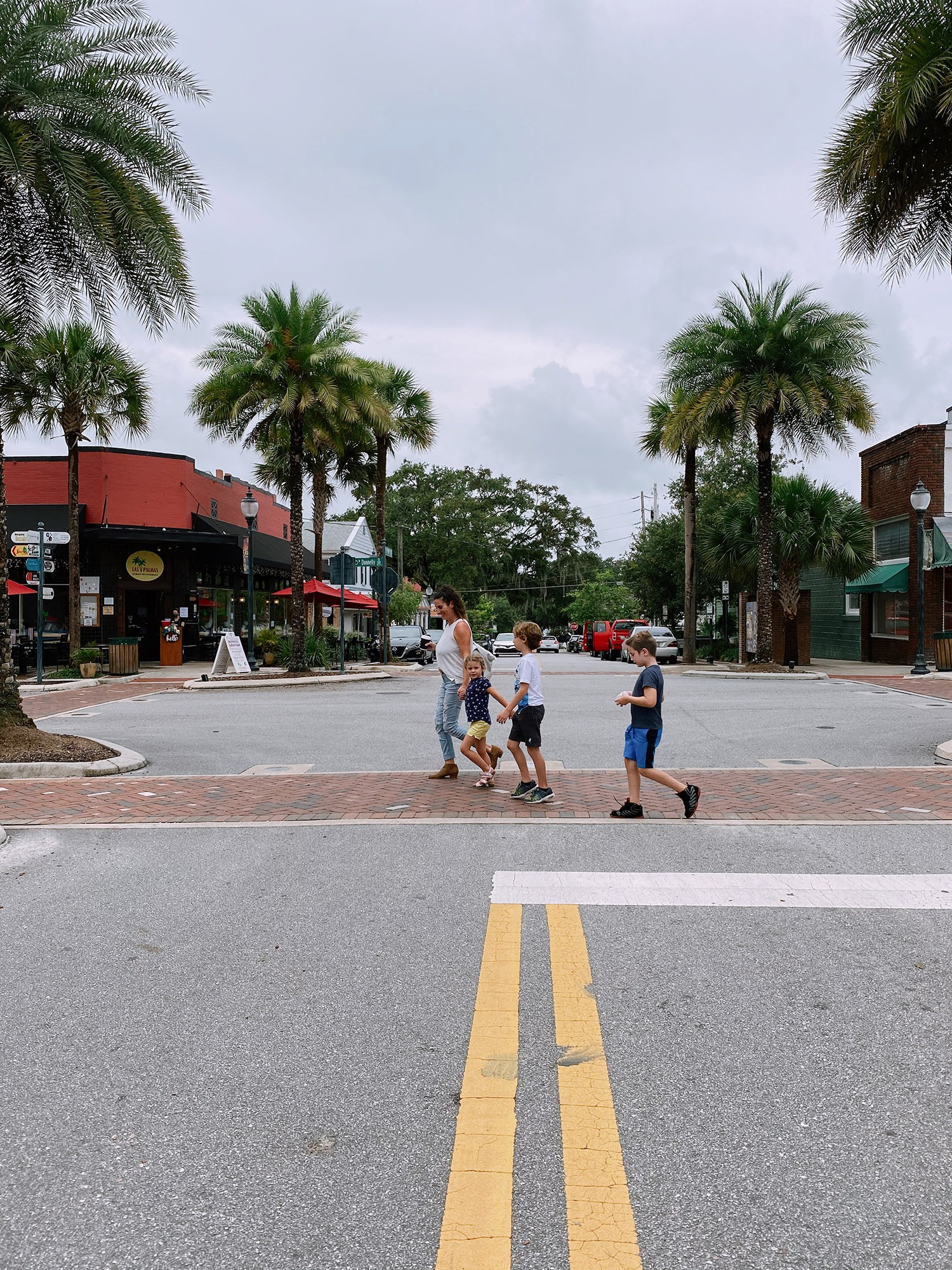 Spectacular Lake County, Florida Staycation Ideas for the Family! Downtown Mount Dora   Lake County by popular Florida blog, Fresh Mommy Blog: image of a mom and her kids walking a cross a street.