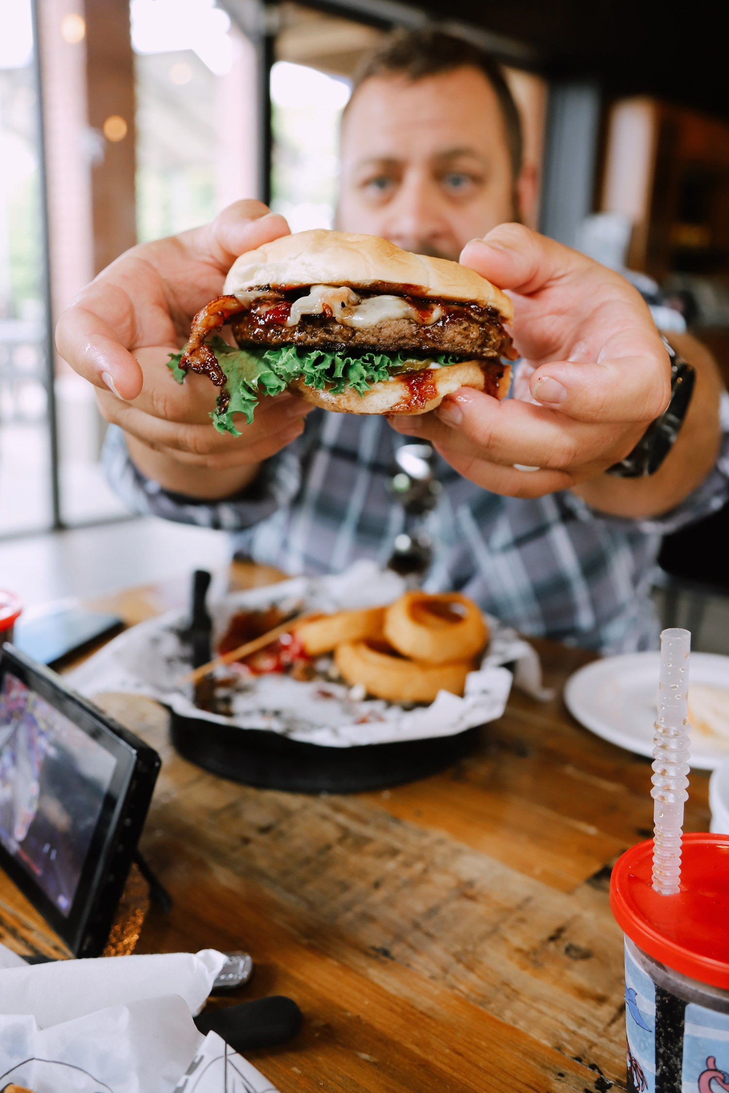Spectacular Lake County, Florida Staycation Ideas for the Family! Bacon Brie Burger at Puddle Jumpers   Lake County by popular Florida blog, Fresh Mommy Blog: image of a man holding a brie burger at Puddle Jumpers.