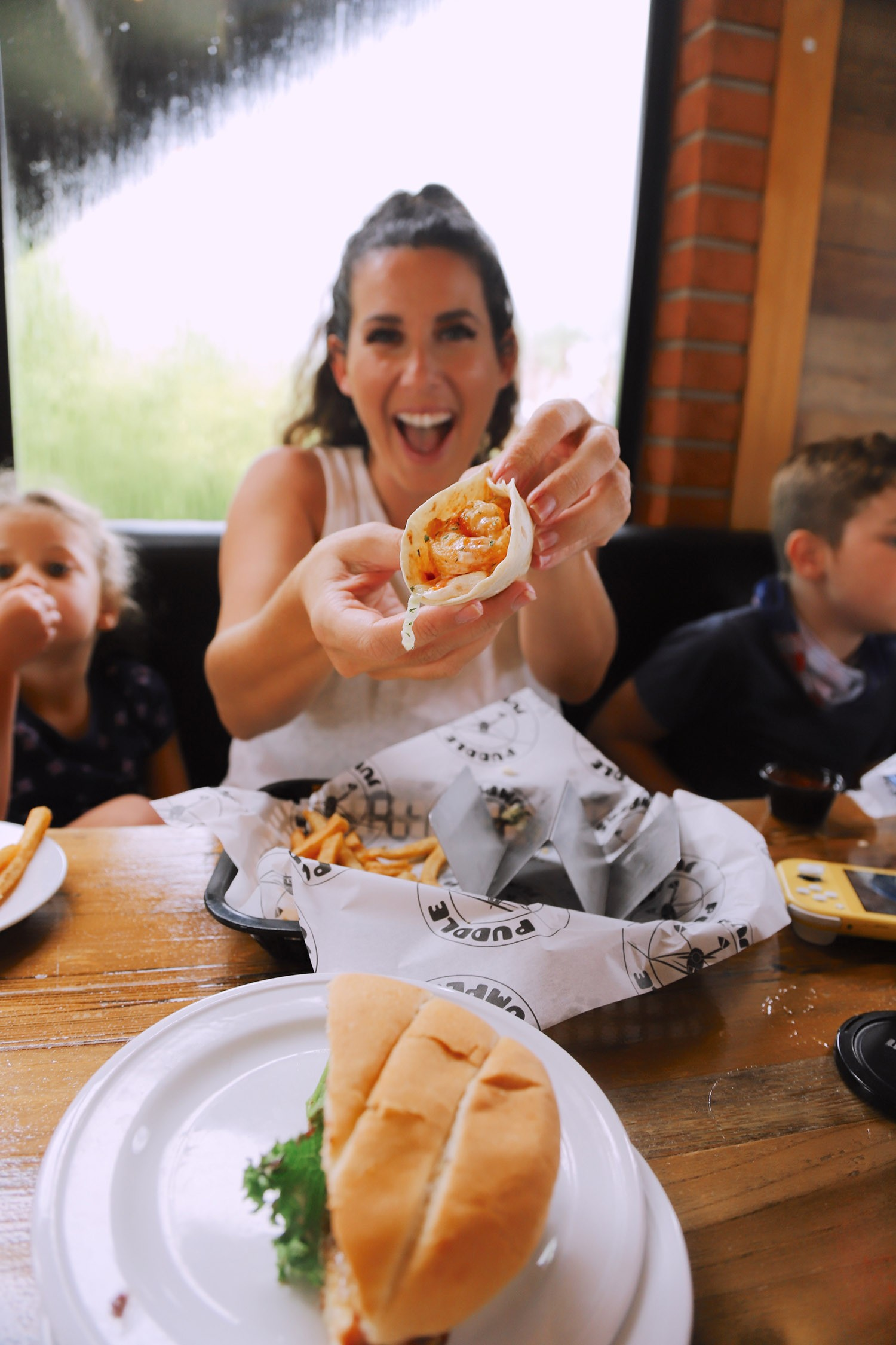 Spectacular Lake County, Florida Staycation Ideas for the Family! Spicy Shrimp Tacos at Puddle Jumpers   Lake County by popular Florida blog, Fresh Mommy Blog: image of a family eating food at Puddle Jumpers.