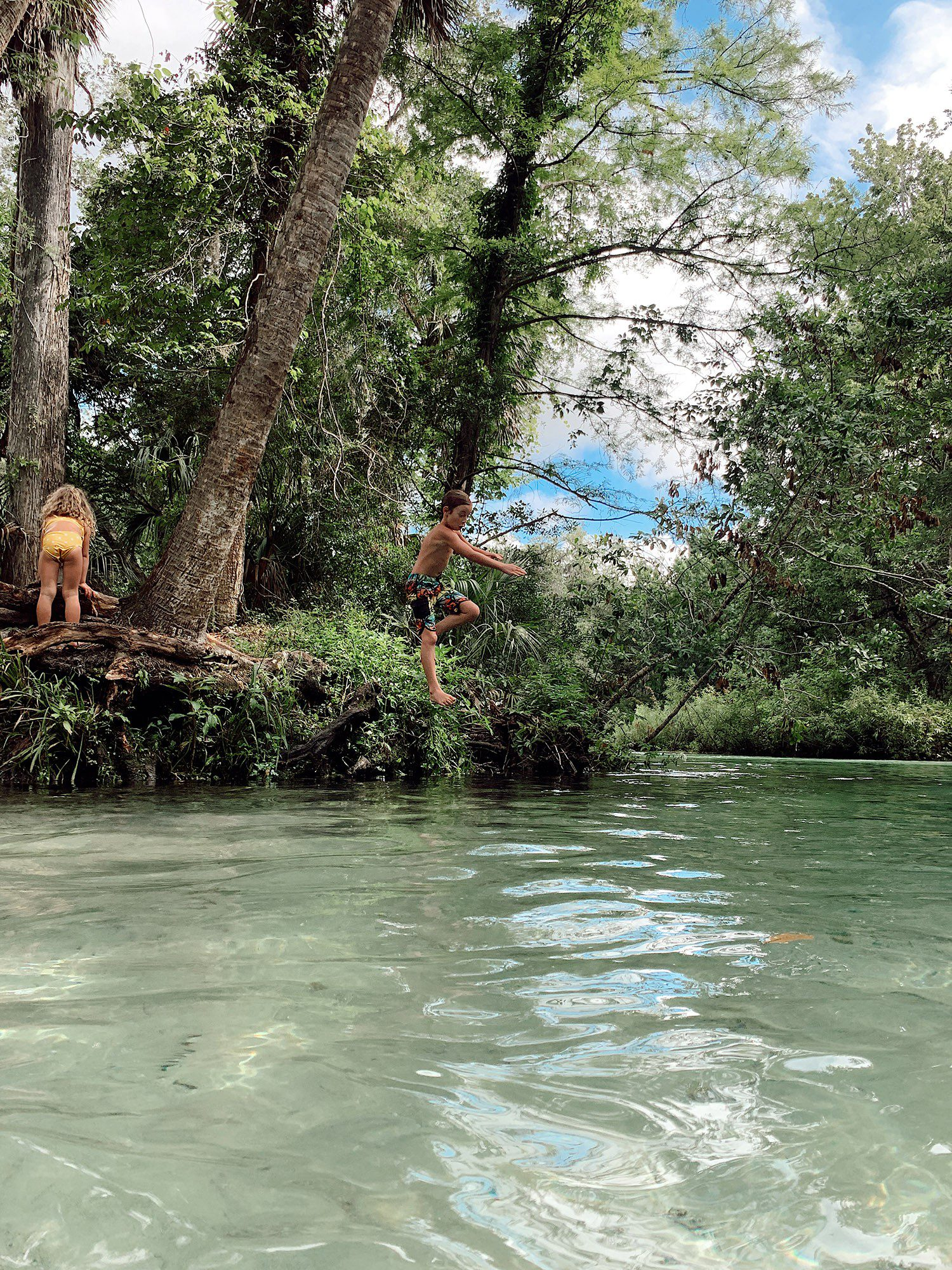 Tips for an Amazing Weeki Wachee Kayaking Florida Staycation. Visit Florida Travel ideas from top lifestyle blogger Tabitha Blue of Fresh Mommy Blog.   Weeki Wachee Kayaking by popular Florida blog, Fresh Mommy Blog: image of a boy jumping into the water.