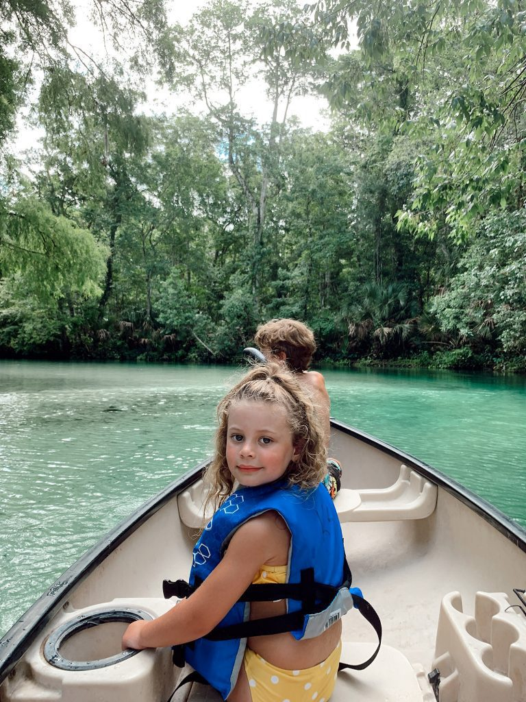 Tips for an Amazing Weeki Wachee Kayaking Florida Staycation. Visit Florida Travel ideas from top lifestyle blogger Tabitha Blue of Fresh Mommy Blog.   Weeki Wachee Kayaking by popular Florida blog, Fresh Mommy Blog: image of a little girl wearing a yellow and white polka dot bikini as she sits in a canoe.