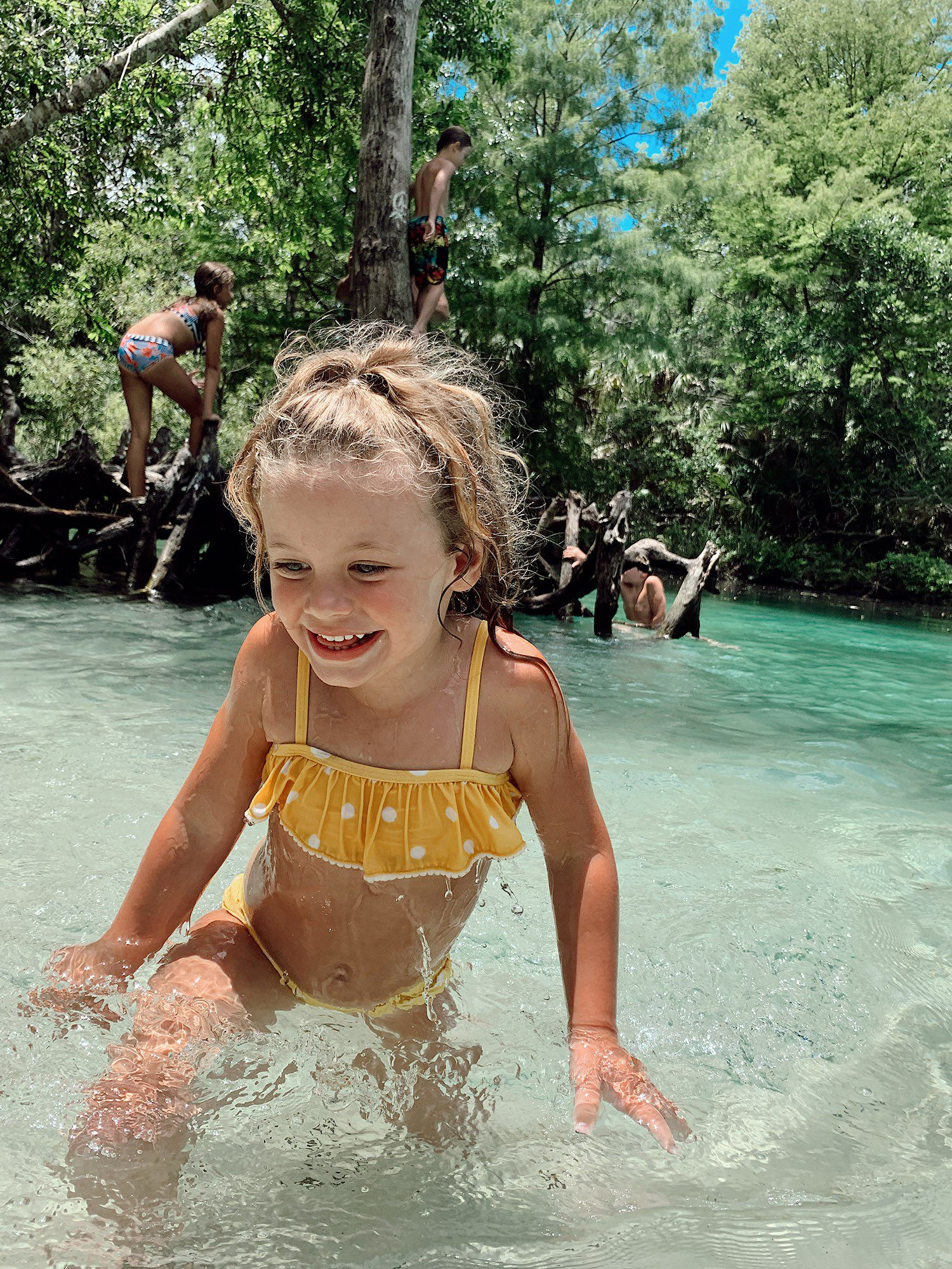 Tips for an Amazing Weeki Wachee Kayaking Florida Staycation. Visit Florida Travel ideas from top lifestyle blogger Tabitha Blue of Fresh Mommy Blog.   Weeki Wachee Kayaking by popular Florida blog, Fresh Mommy Blog: image of a little girl wearing a yellow and white polka dot bikini and playing in the water.