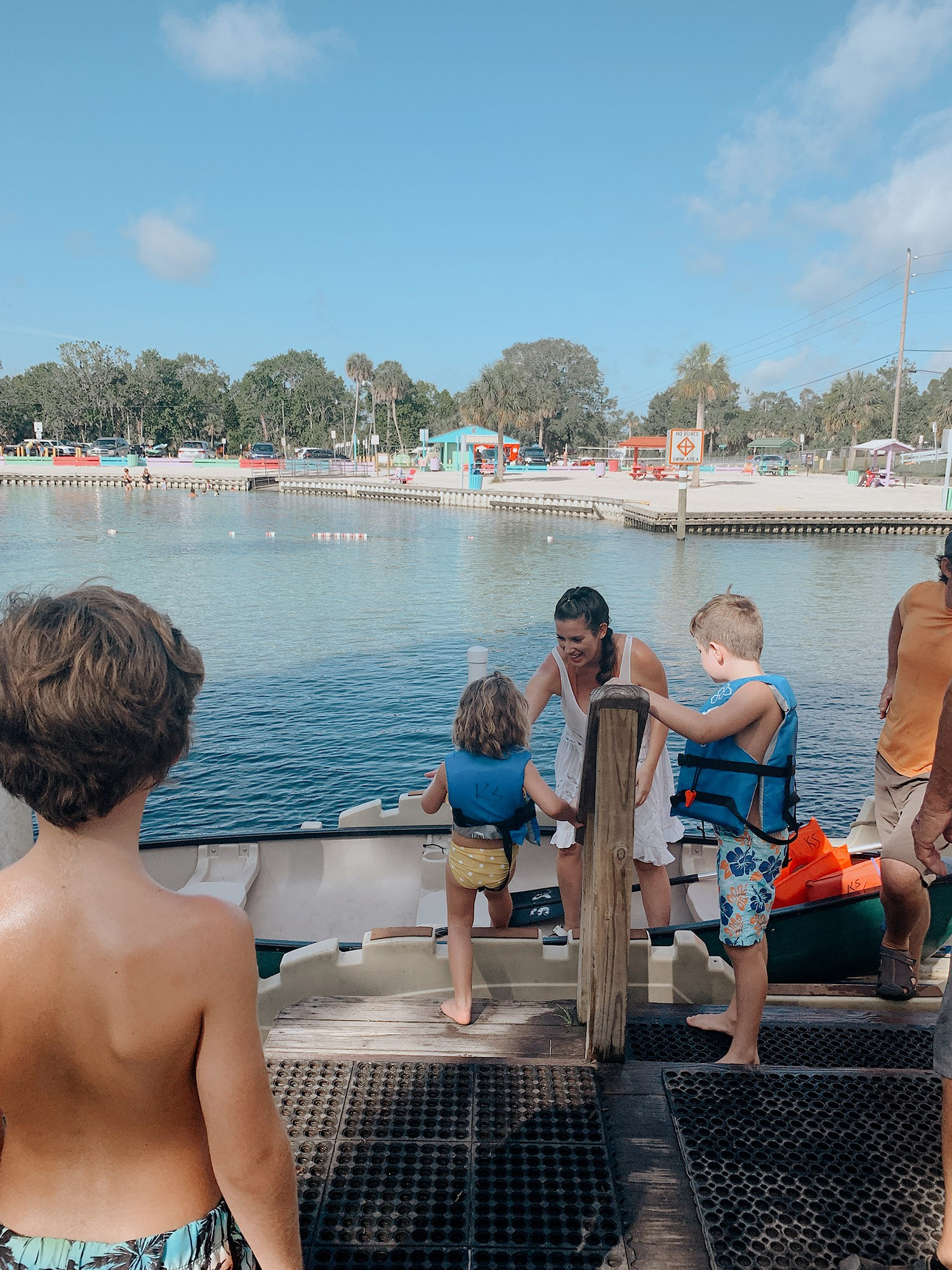 Tips for an Amazing Weeki Wachee Kayaking Florida Staycation. Visit Florida Travel ideas from top lifestyle blogger Tabitha Blue of Fresh Mommy Blog.   Weeki Wachee Kayaking by popular Florida blog, Fresh Mommy Blog: image of Tabitha Blue helping her kids climb into a canoe.