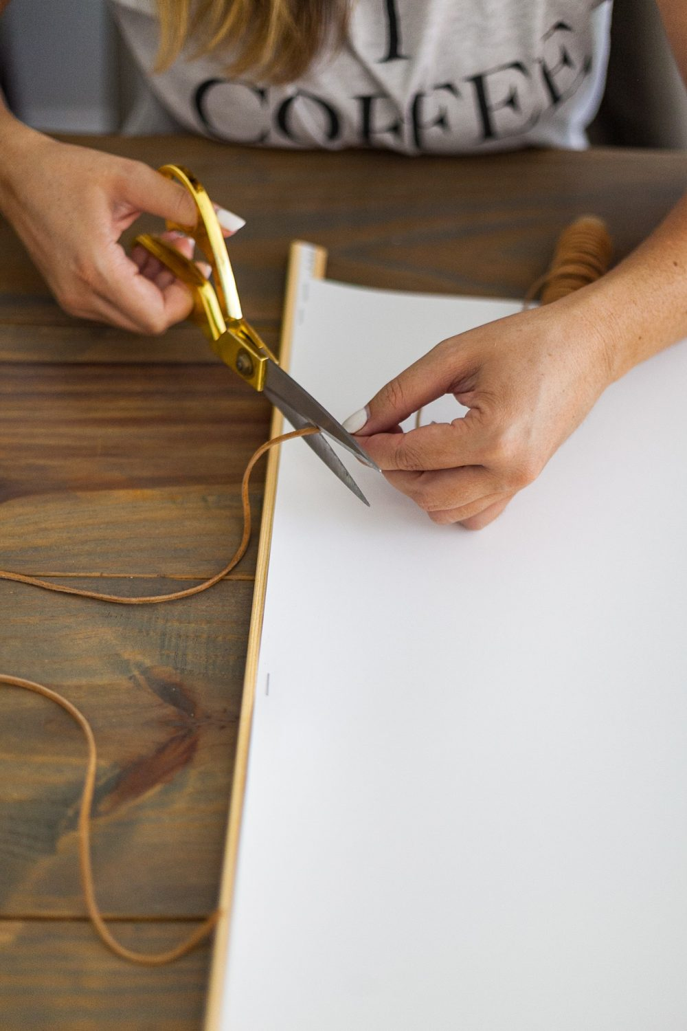 Click through for a fun, EASY DIY poster hanger tutorial. You can make your own DIY poster hanger for $3 in just a few short minutes!   DIY Poster Hanger by popular Florida DIY blog, Fresh Mommy Blog: image of a woman cutting some suede cord with a pair of gold scissors.