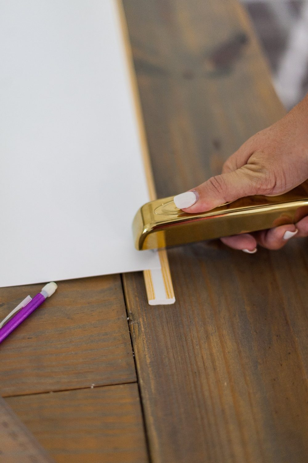 Click through for a fun, EASY DIY poster hanger tutorial. You can make your own DIY poster hanger for $3 in just a few short minutes!   DIY Poster Hanger by popular Florida DIY blog, Fresh Mommy Blog: image of a woman attaching a poster board to some wood moulding with a gold stapler.