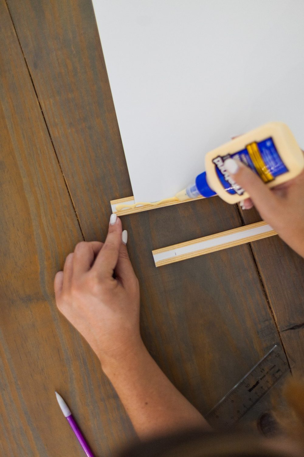 Click through for a fun, EASY DIY poster hanger tutorial. You can make your own DIY poster hanger for $3 in just a few short minutes!   DIY Poster Hanger by popular Florida DIY blog, Fresh Mommy Blog: image of a woman applying wood glue to the back of a poster board that's been attached to some wood moulding.