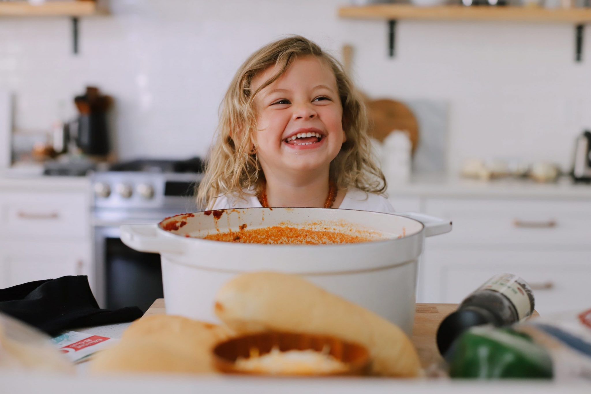 Easy Family Favorite Chili recipe! Make this delicious classic homemade chili in the crockpot or in one pot easily. It's THE BEST CHILI, and my family asks me to make it over and over. |  Chili Recipe by popular Florida lifestyle blog, Fresh Mommy Blog: image of a young girl standing in front of a pot of chili.